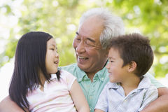Grandfather laughing with grandchildren. Outside royalty free stock photo