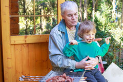 Grandfather and little boy making barbecue and eating grilled me Stock Images