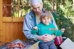 Grandfather and little boy making barbecue and eating grilled me Royalty Free Stock Photography