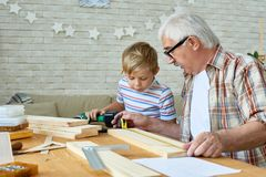Grandfather and Little Boy Making Wooden Models Together Royalty Free Stock Image