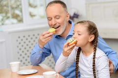 Grandfather and little girl having tea party Stock Images