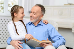 Grandfather with little girl reading book Royalty Free Stock Photos
