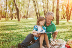 Grandfather with little girl reading Royalty Free Stock Images