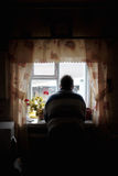 Grandfather looks out window Stock Photos