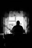 Grandfather looks out window Royalty Free Stock Image