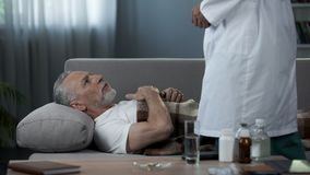 Grandfather lying on couch and complaining doctor of heart pain, healthcare. Stock footage royalty free stock photos