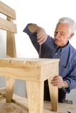 Grandfather makes a chair stock photography