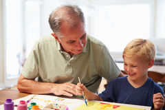 Grandfather Painting Picture With Grandson At Home Stock Photos