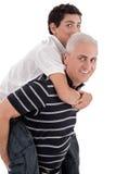 Grandfather piggybacking his grandson Stock Photography