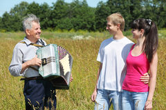 Grandfather play on accordion with couple Stock Photography