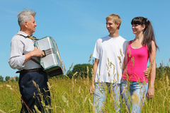 Grandfather play on accordion for couple Royalty Free Stock Image