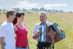 Grandfather play on accordion sing for couple. Grandfather in shirt play on accordion, sing for young couple near village royalty free illustration