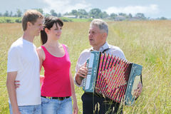 Grandfather play on accordion sing for couple. Grandfather in shirt play on accordion, sing for young couple royalty free illustration