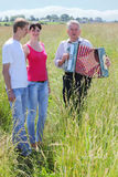 Grandfather play on accordion sing for couple. Grandfather in shirt play on accordion, sing for young couple near village, wood, full body stock illustration