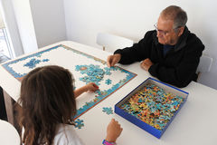 Grandfather play with granddaughter puzzle Royalty Free Stock Photos