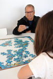 Grandfather play with granddaughter puzzle Stock Image