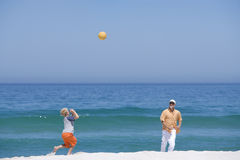 Grandfather playing ball with grandson on beach near ocean Stock Image