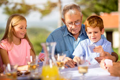 Grandfather is playing cards. With his grandchildren Royalty Free Stock Image