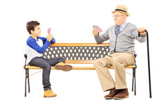 Grandfather playing cards with his nephew seated on bench. Isolated on white background Royalty Free Stock Photography
