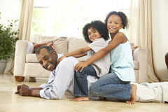 Grandfather Playing With Grandchildren At Home. Smiling To Camera royalty free stock photo