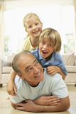 Grandfather Playing With Grandchildren At Home Royalty Free Stock Photography