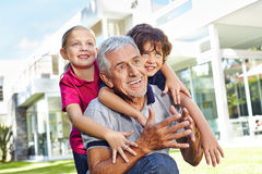 Grandfather playing with grandchildren in summer. Happy grandfather playing with his two grandchildren in a garden in summer Royalty Free Stock Image