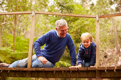 Grandfather playing with grandson on a bridge in a forest Royalty Free Stock Images