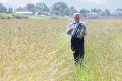 Grandfather plays accordion in field Stock Photos