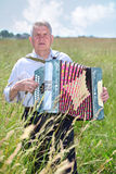 Grandfather plays accordion in field Royalty Free Stock Photography