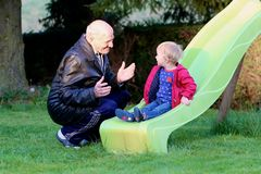 Grandfather plays with granddaughter on playground Stock Images