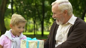 Grandfather presenting birthday giftbox to his grandson, celebration, happiness stock video footage