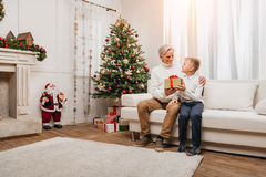 Grandfather presenting christmas gift to grandson Royalty Free Stock Photos