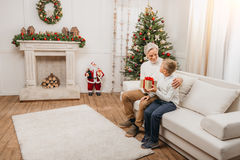 Grandfather presenting christmas gift to grandson Royalty Free Stock Images