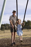 Grandfather pushes girl on a swing Royalty Free Stock Images