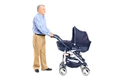 Grandfather pushing a baby stroller Royalty Free Stock Images
