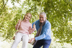 Grandfather pushing granddaughter on swing Royalty Free Stock Photo
