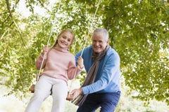 Grandfather pushing granddaughter on swing. Grandfather puching granddaughter on garden swing Royalty Free Stock Photo