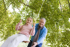 Grandfather pushing granddaughter on swing Royalty Free Stock Photography