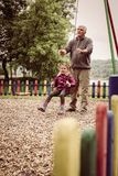 Grandfather pushing granddaughter on swing. Royalty Free Stock Photo
