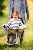 Grandfather pushing his grandaughter in a wheelbarrow. Royalty Free Stock Photos