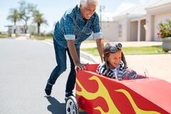 Free Grandfather Pushing His Little Boy On Toy Car Stock Photos - 190532923