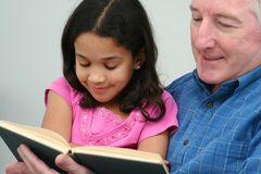 Grandfather Reading Book. Grandfather reading a book to his granddaughter Royalty Free Stock Photo