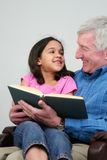 Grandfather Reading Book. Grandfather reading a book to his granddaughter Royalty Free Stock Photos
