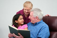 Grandfather Reading Book. Grandfather and Grandmother reading a book to their granddaughter Royalty Free Stock Photo