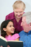 Grandfather Reading Book. Grandfather and Grandmother reading a book to their granddaughter Stock Images