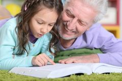 Grandfather reading book with  grandaughter. Grandfather reading book with his little  granddaughter Royalty Free Stock Photos