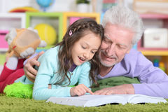 Grandfather reading book with  grandaughter Royalty Free Stock Images