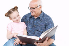 Grandfather reading a book with granddaughter Royalty Free Stock Photography