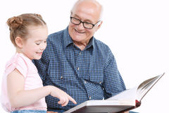 Grandfather reading a book with granddaughter Stock Photo