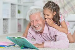 Grandfather reading book with his granddaughter. Grandfather reading book with his little granddaughter Royalty Free Stock Images